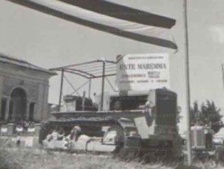 """1)Assegnazione dei poderi a Castel di Guido. Su un cartello appoggiato alla macchina agricola si legge: """"Ente Maremma. Azienda di riforma di Muratella"""" •data20.07.1952 •stampa fotografica-b/n"""