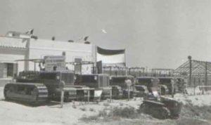"""2)Castel di Guido. Esposizioni di trattori in occasione della cerimonia di assegnazione delle terre. Su un cartello appoggiato ad una macchina agricola si legge: """"Ente Maremma. Azienda di sviluppo"""" •data20.07.1952"""